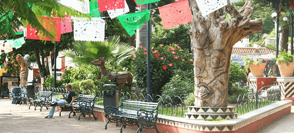 Main plaza of Ajijic with green bench chairs and a gardener with trees