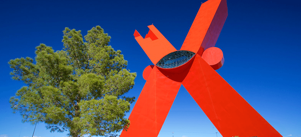 X shape red monument next to a green tree
