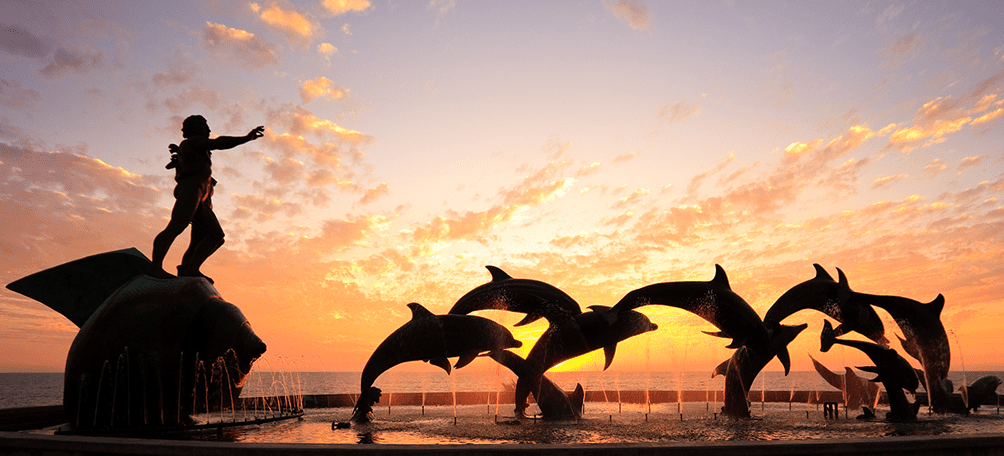 Statue of dolphin jumping with a bright sunset